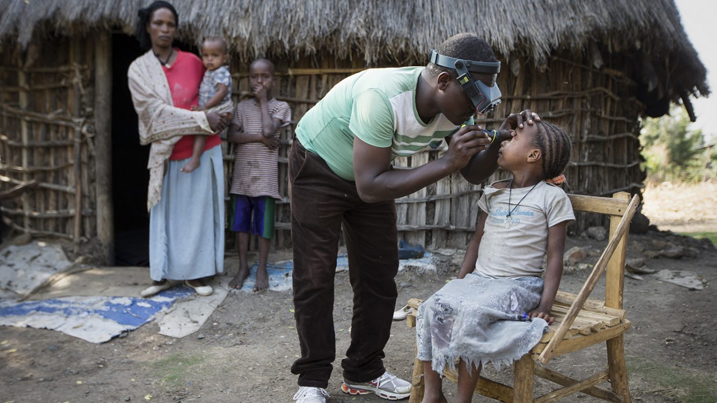 A child is sitting on a wooden chair. A health worker is examining their eyes. Hibret and two other children are standing, watching in the background.