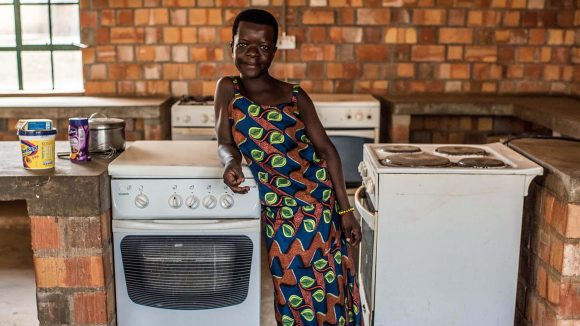 Woman standing between two stoves.