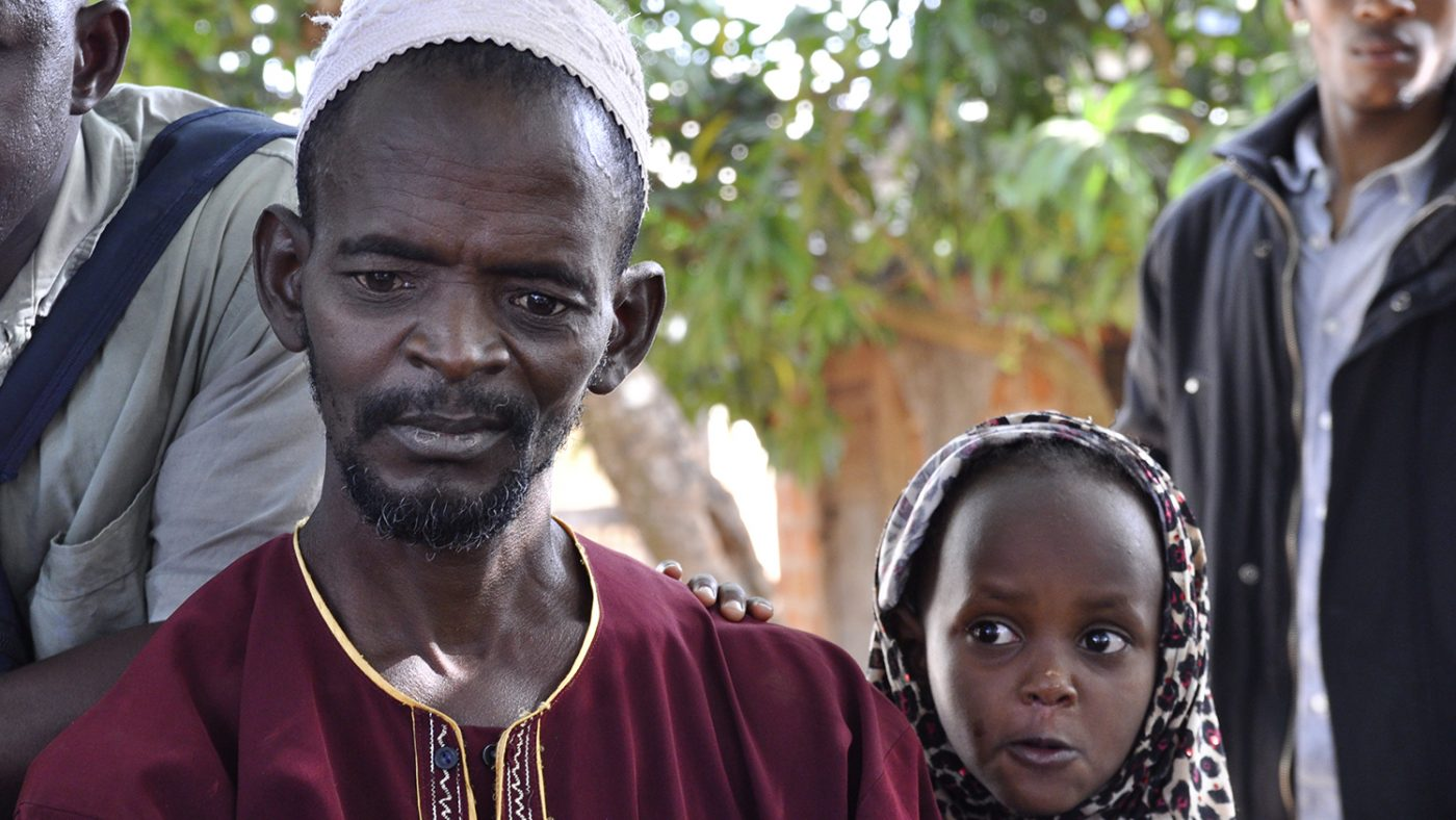 Mamadou wears maroon robe with a white cap and his daughter Rougiatou Bah wears a leopard print headscarf. Mamadou is holding his daughter in his arms.