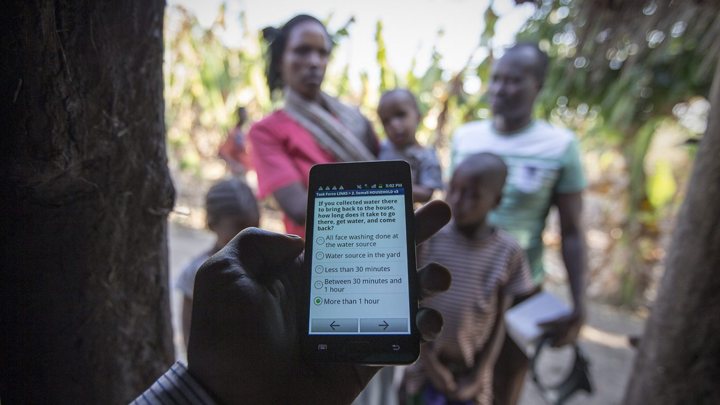 A hand is holding a mobile phone. On the screen it reads: If you collected water there to bring back to the house, how long does it take to go there, get water and come back? The answer: More than 1 hour, is ticked.