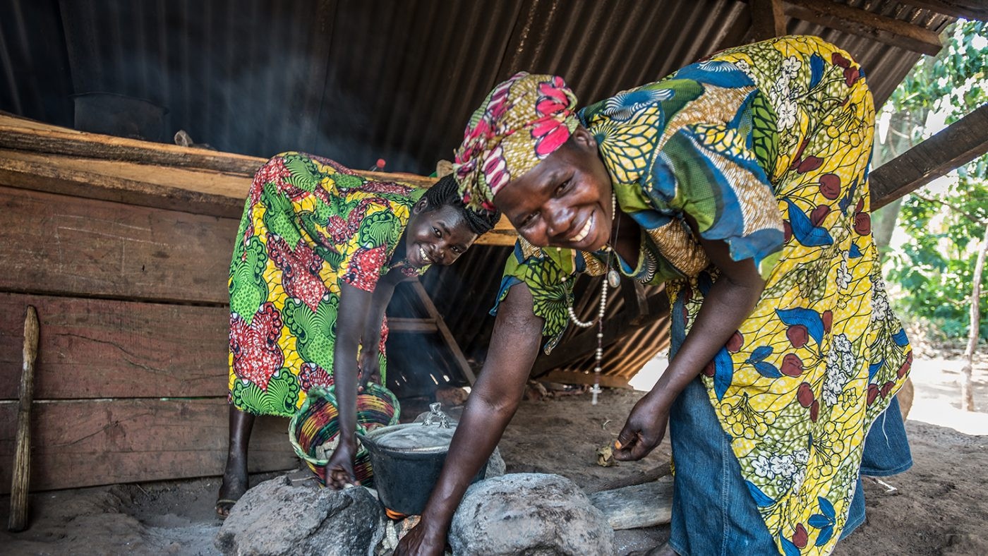 Monica and her mother are smiling and leaning over a pot, cooking on an open fire outside.