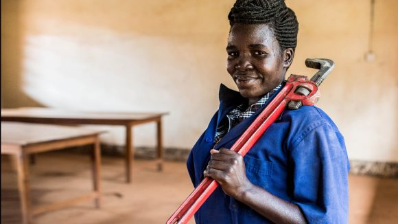Monica Friday photographed in her classroom on the first day of her plumbing course at the Nile Vocational Training Institute in Hoima, Uganda. She is dressed in blue overalls and holding a wrench.