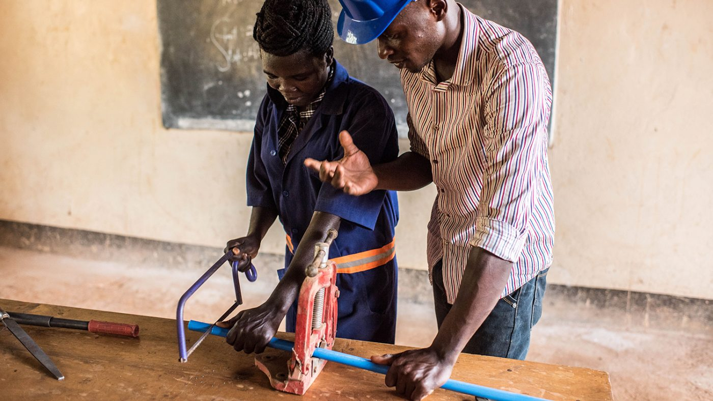 Monica Friday takes a lesson from her instructor, Julius Peter Eperu, on the first day of her plumbing course.