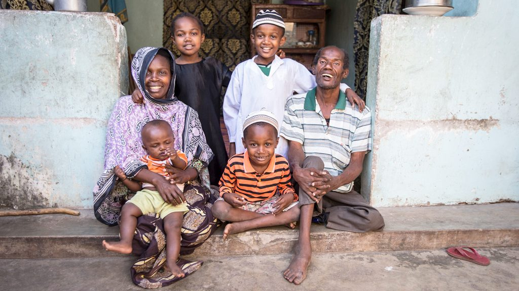 A family sit outside their home and joyfully pose for the camera.