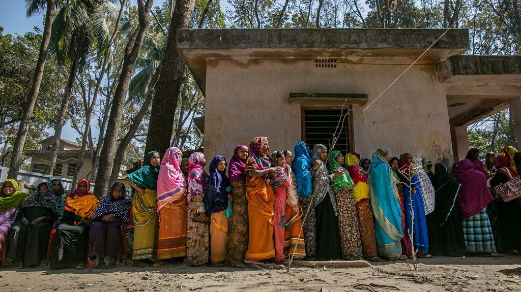 Women wearing bright colours, queue for an eye health screening in Bangladesh.