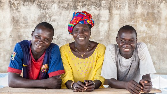 Three people sit behind a desk smiling.