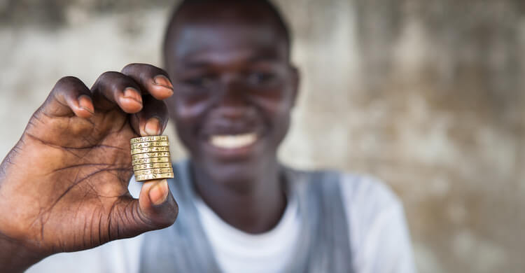 A boy holding one pound coins
