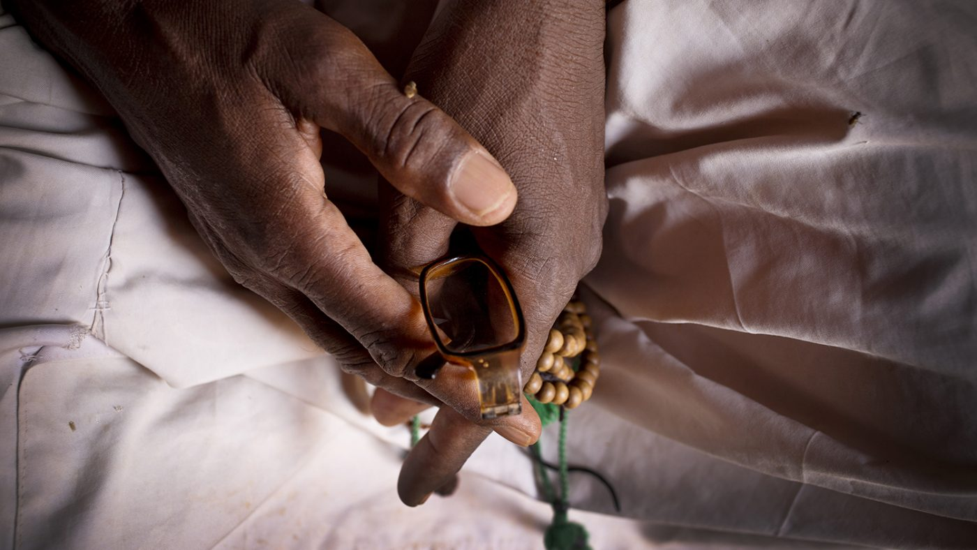 A close-up of Issa's hands as he clutches his spectacles and his prayer beads.