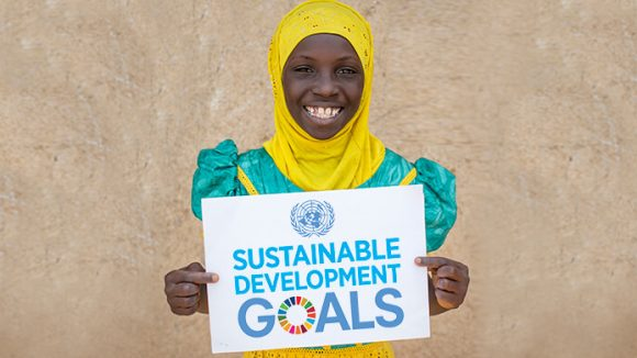 A girl holding a card saying 'sustainable development goals'.