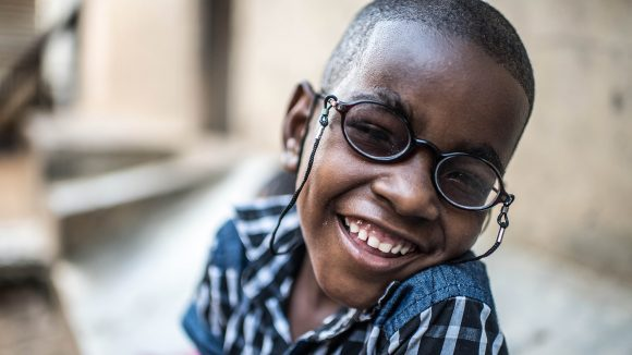 Sadhi, a young boy, wearing glasses and smiling