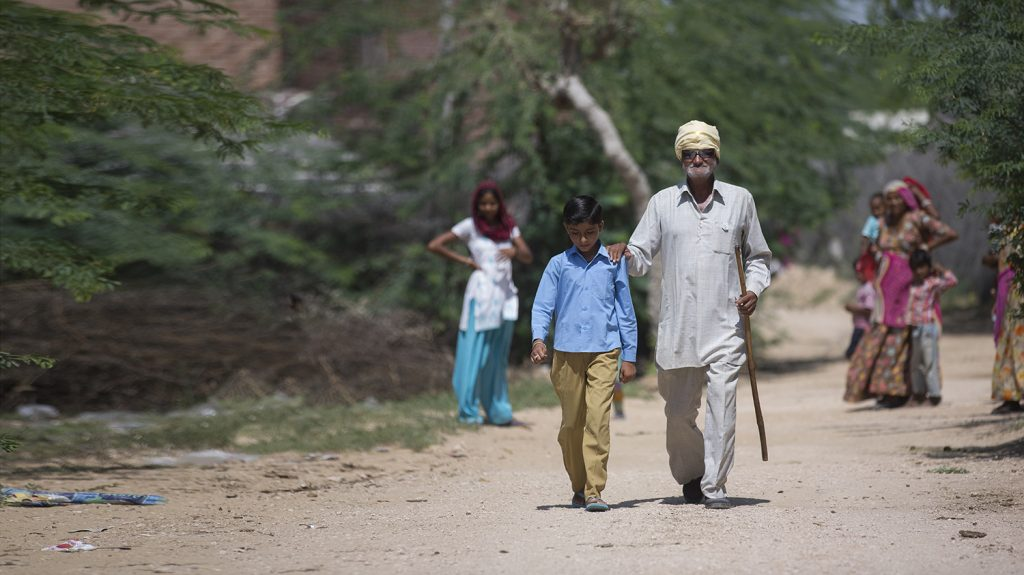 Sankarlal walking with his son. He is wearing dark glasses, carrying a cane and has his hand on his 12 year old son's shoulder to guide him down a dusty road.
