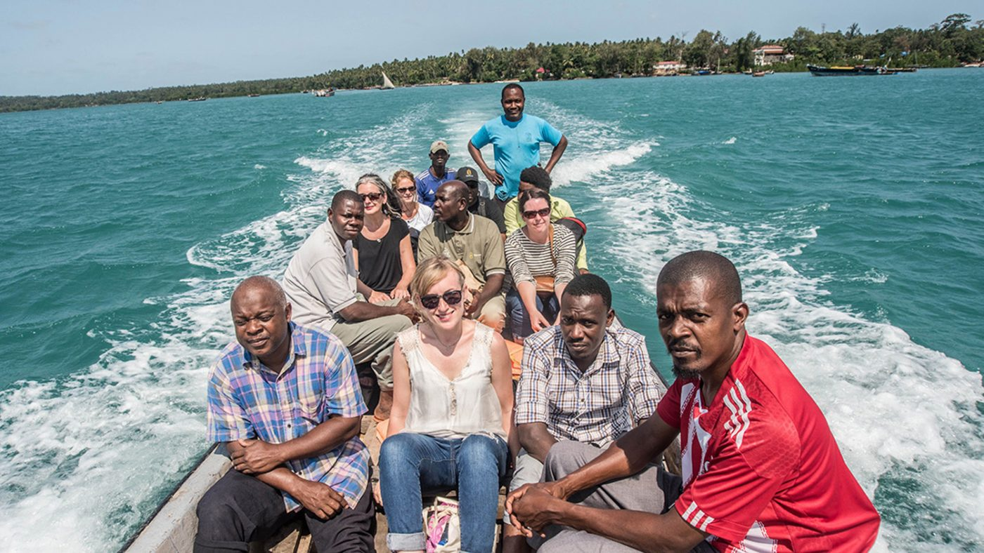 Sarah, Sightsavers employee, sitting on a boat with 12 other people. The boat is travelling along the sea.