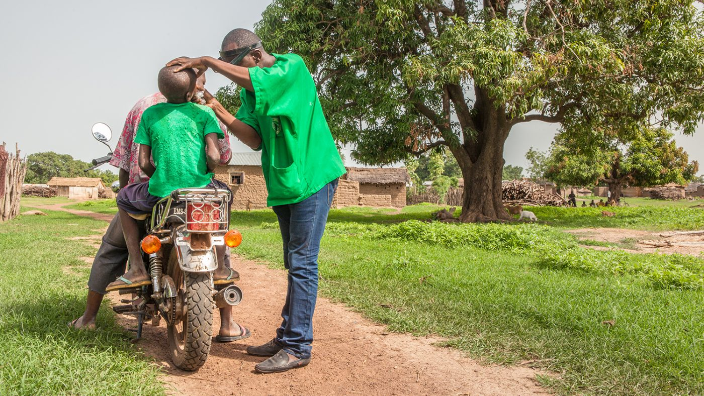 Mobile surgeon Boubacar Fomba examines a boy's eyes as he sits on a motorbike in Mali.