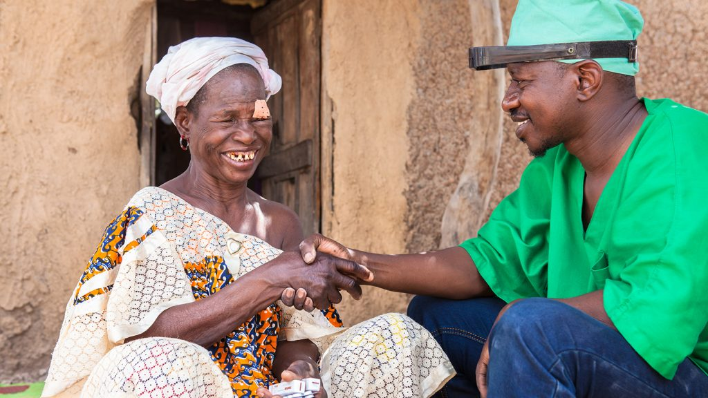 Mobile surgeon Boubacar Fomba shakes the hand of patient Kany Doumbia following her trichiasis surgery.