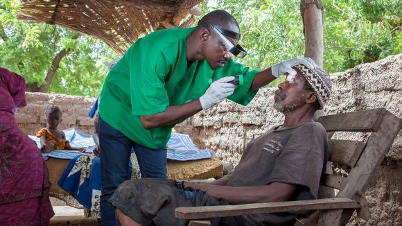 Mobile surgeon Boubacar Fomba uses a torch to examine a patient's eyes in Mali.