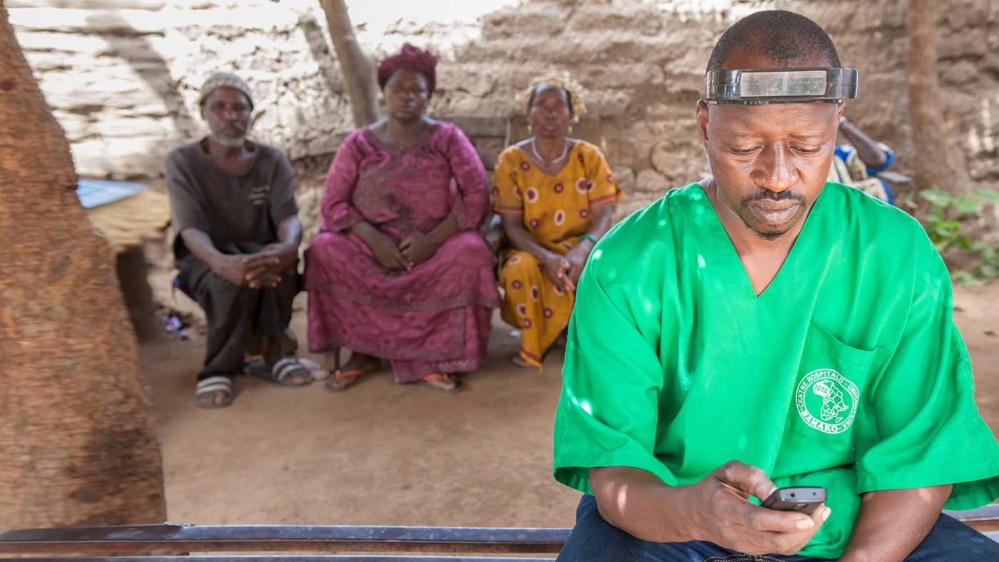 Mobile surgeon Boubacar Fomba checks his mobile phone.