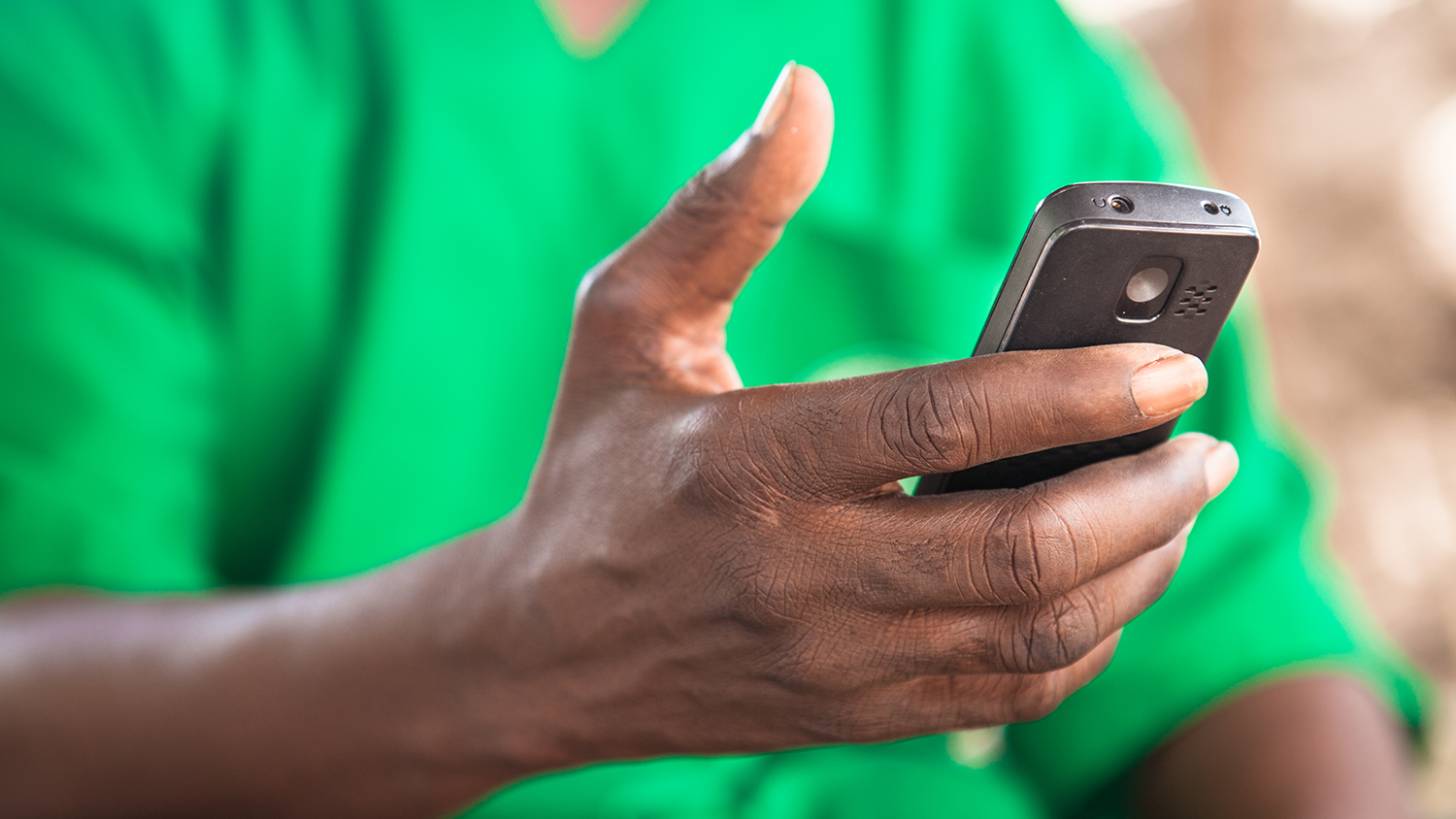 A close-up of mobile surgeon Boubacar Fomba checking his mobile phone.