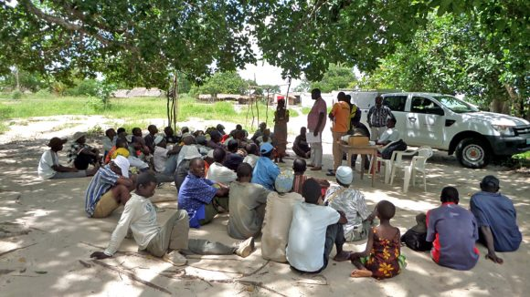 A group of villagers sit on the ground under a tree during a CATCH screening camp in Mozambique.