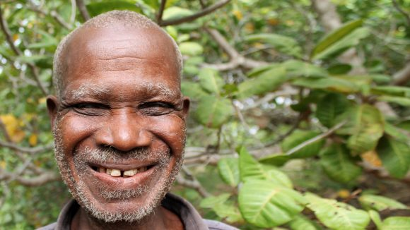 Emmanuel smiling while standing in front of a tree.
