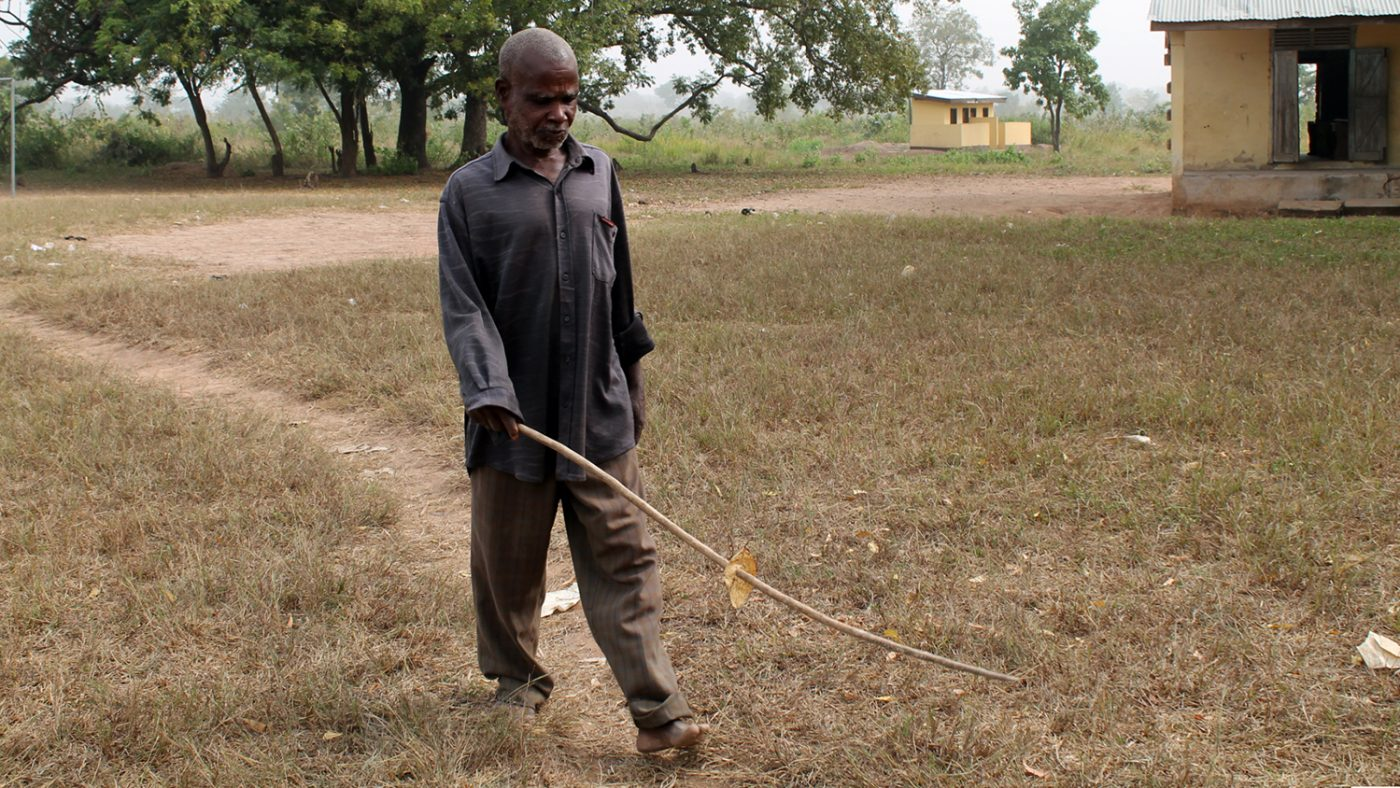 Emmanuel walks through the fields outside his village, carrying his long white cane.