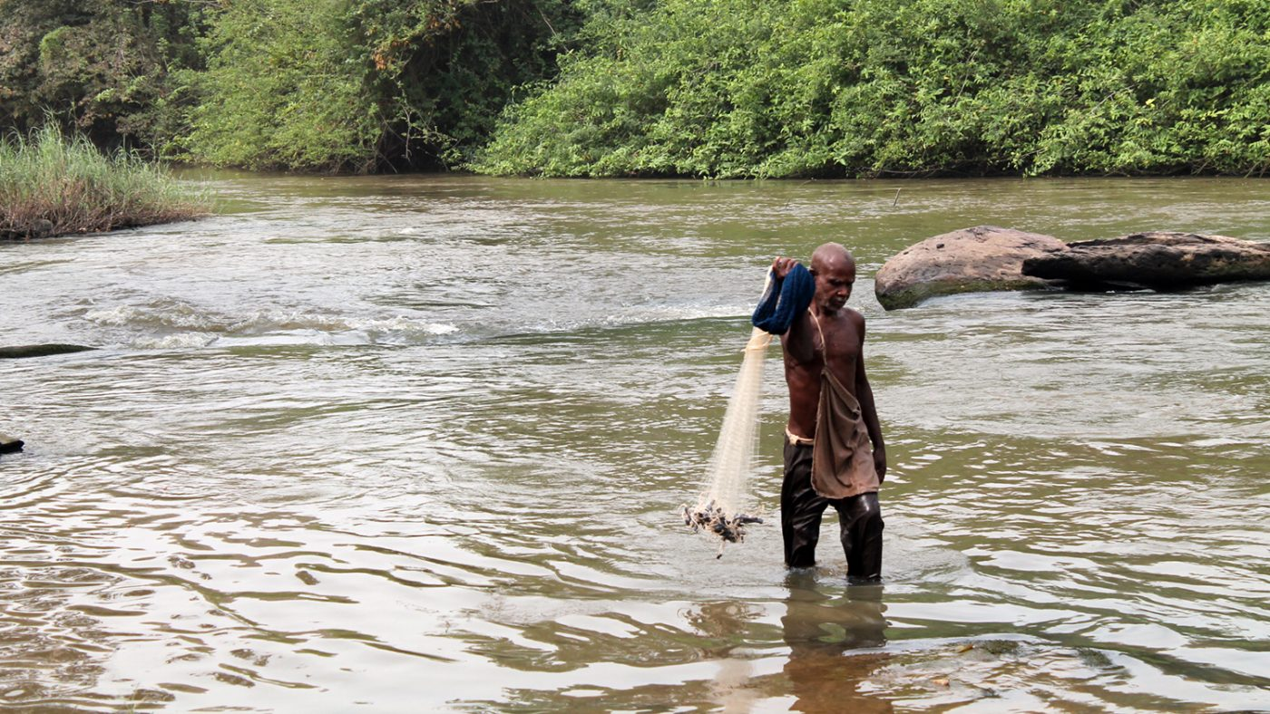 Emmanuel fishing in the Pru River: he stands in knee-deep water while holding a fishing net.