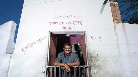 A photo from the Sightsavers Framing Perceptions exhibition by Graeme Robertson, showing a smiling man standing at the doorway of a home in India.