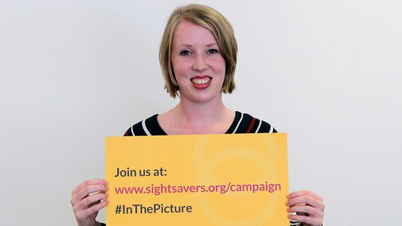 Paralympian Georgie Bullen holds a yellow sign containing the words: 'Join us at www.sightsavers.org/campaign, #inthepicture'.