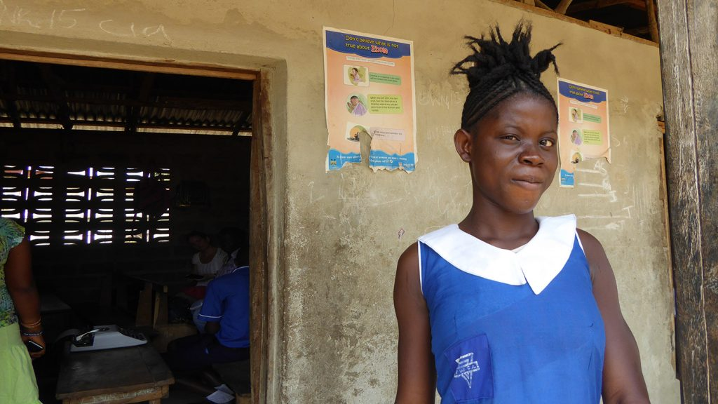 5-year-old Jenneh from Sierra Leone, who is blind, stands outside her school building wearing her blue school uniform.
