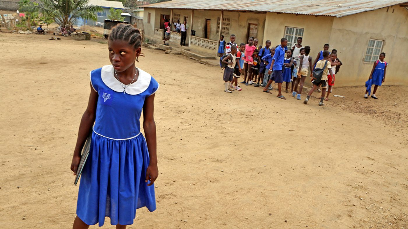 Jenne stands outside her school in Bo, Sierra Leone, with her classmates in the background.