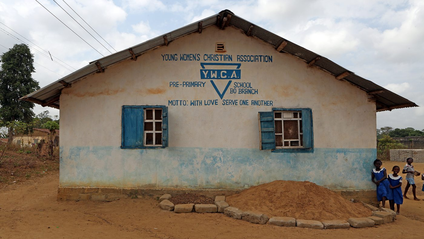Jenneh's school: a small white hut with words painted on the outside, saying