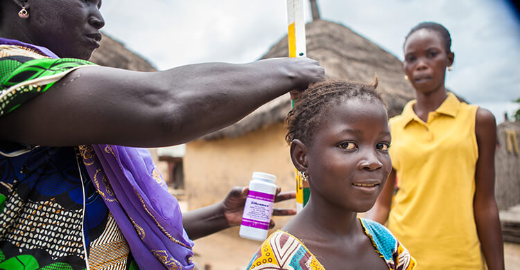 A girl in Senegal is measured with a dose pole to find out how much medication she needs to take, as part of a mass drug administration campaign to prevent the spread of trachoma.