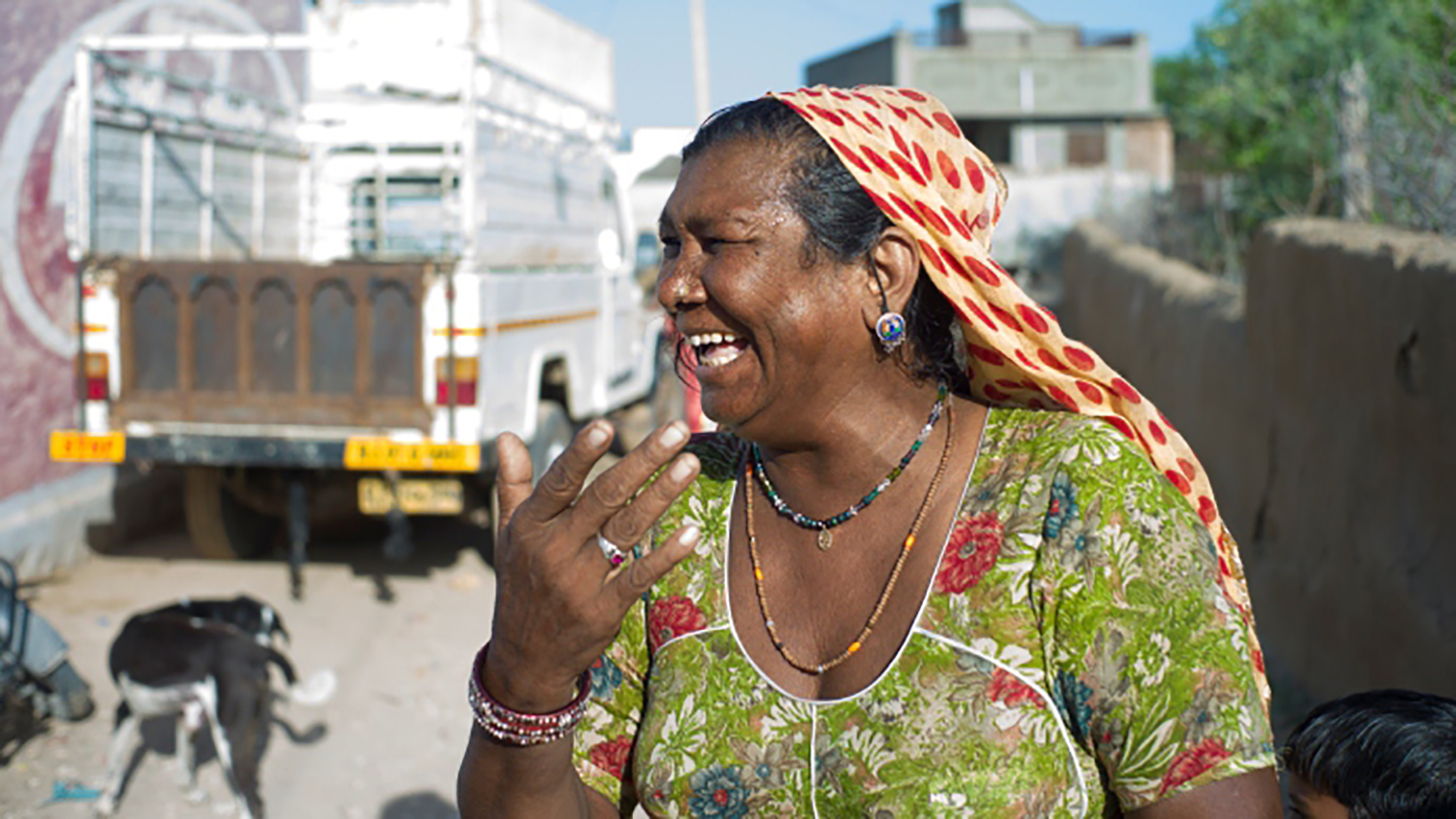 A woman in New Delhi, India, laughs as she stands on the street in front of a truck.