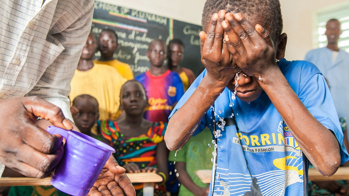 A schoolboy splashes water on his face to learn about facewashing, as part of a SAFE initiative in Senegal.