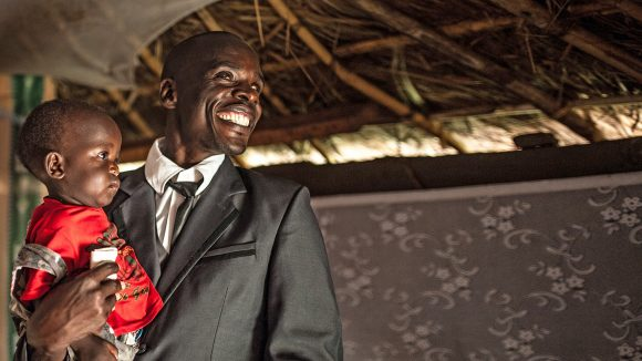 Simon Peter Otoyo smiles as he holds his son, 10-month-old Komagum Joshua, inside his home in Bweyale, Uganda.