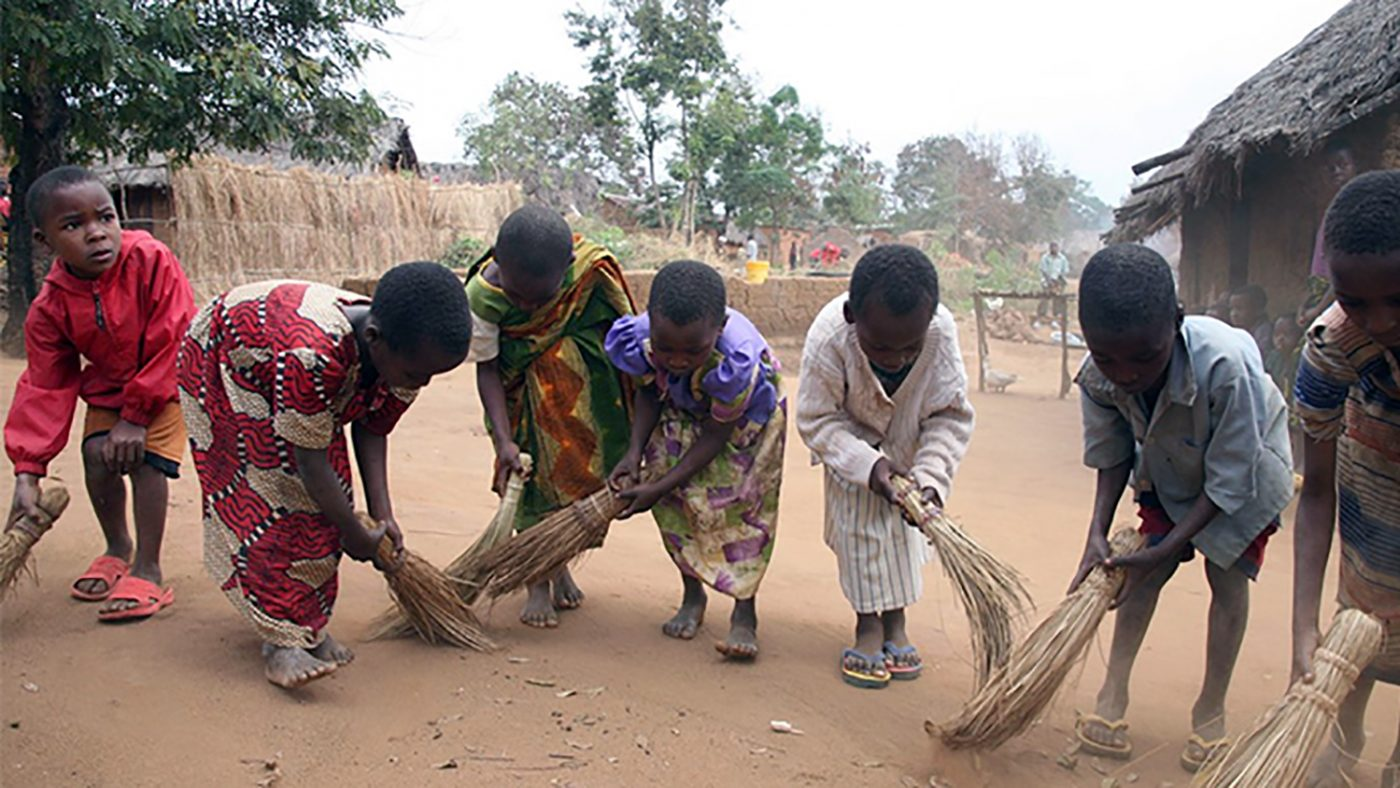 A group of children in Tanzania using brooms to sweep outside their homes.