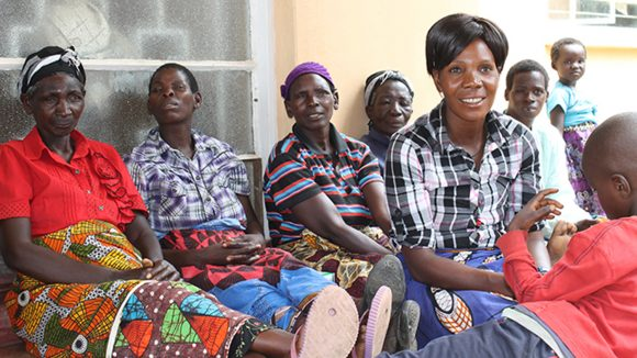 A group of trichiasis patients sit outside the health centre in Mwase village.