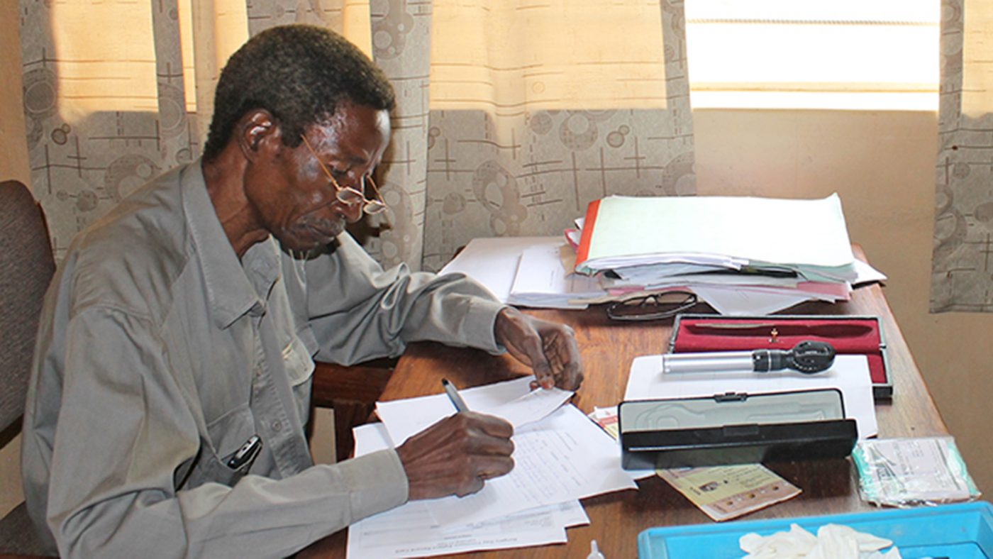 Cataract and TT surgeon Mr Limwanya works at his desk in the office at the hospital.