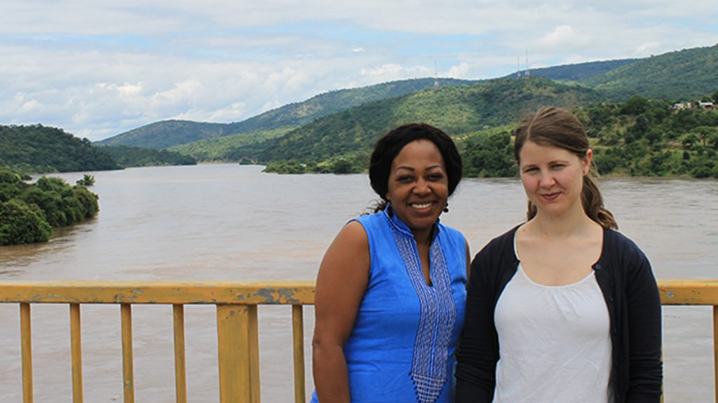 Glenda and Moa standing on a bridge of the Lwangwa river in Zambia. Behind them is the muddy, swollen river with green trees either side.