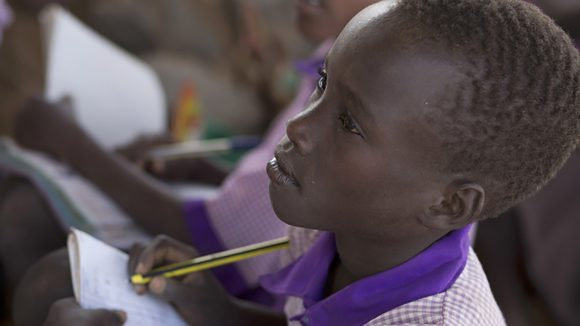 A schoolboy in Kenya sits in the classroom holding pencil and paper while listening to the teacher.
