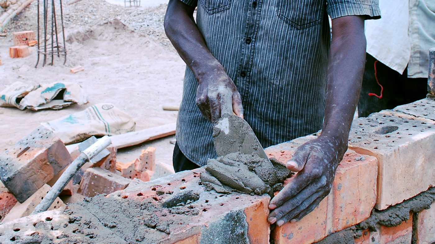 A close-up of a man working on a construction site, laying cement onto bricks to build a wall.