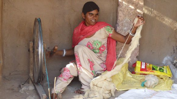 A woman in India with visual impairments weaving wool in her home.