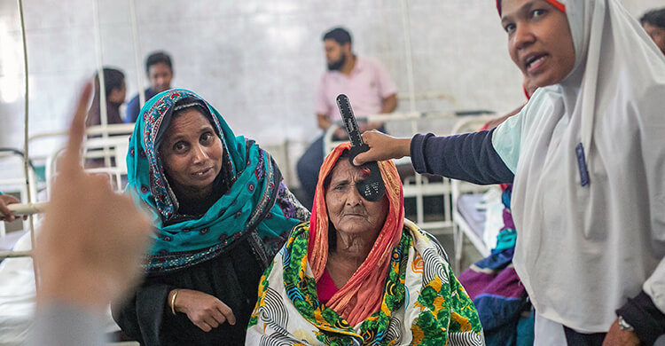 An elderly woman in Bangladesh has her eyes tested, A doctor covers one of her eyes while a nurse stands at a distance and holds up one finger.