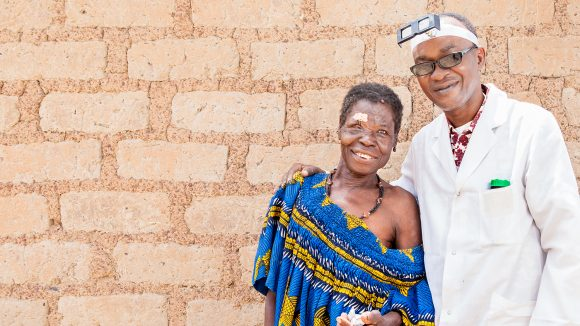 A surgeon in Mali stands next to his female patient following her eye surgery. Both are smiling.