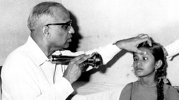 A doctor examines a girl's eyes in India in the 1950s.