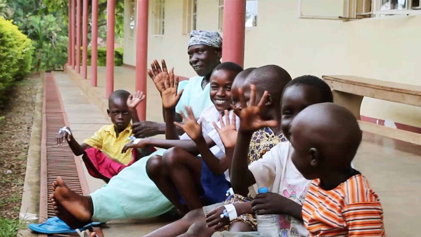 Group of children and a women sitting by an African railway station and waving to camera