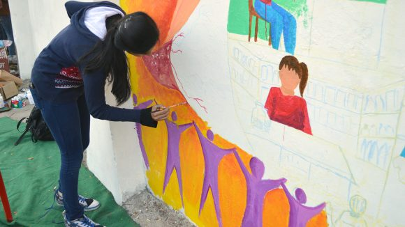 Art student painting the Inclusive Eye Health mural in Bhopal.