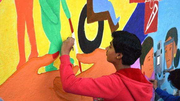 Art student putting finishing touches to the Inclusive Eye Health mural in Bhopal.