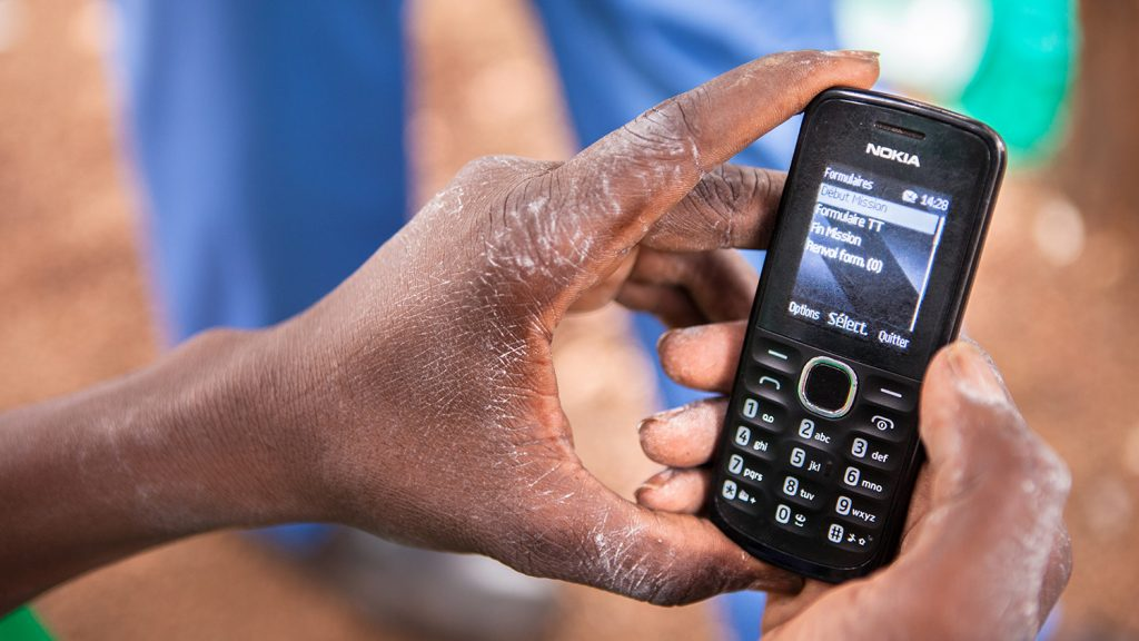 A close-up of a doctor holding a mobile phone.