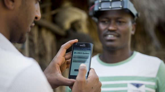 Eye health workers in Ethiopia gather data using mobile phone.