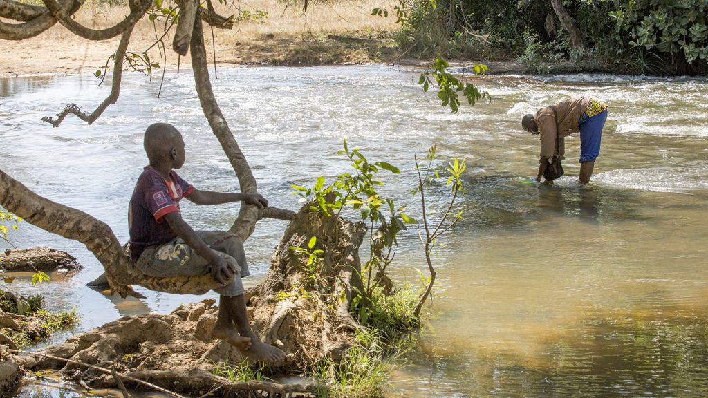 A boy and his father amid a fast-flowing river, where the black flies that carry the river blindness parasite like to breed.